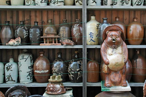 Old-style tanuki figure and big sake bottles